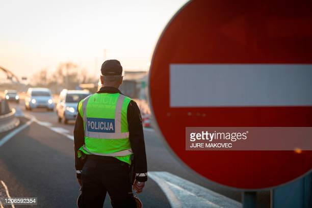 A Slovenian police officer controls traffic at the SlovenianItalian border crossing near Nova Gorica on March 11 after Slovenia's government...