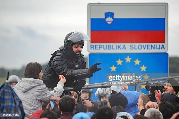A Slovenian police officer gives instructions as migrants and refugees wait to cross the CroatiaSlovenia border on October 19 2015 in Trnovec...