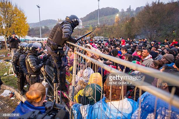 A Slovenian policeman goes over a fence to rescue a child pushed by the crowd against the fence as migrants and refugees wait to cross the...