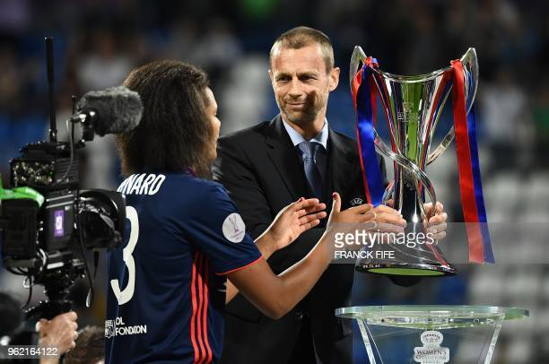 Slovenian president Aleksander Ceferin handovers Olympique Lyonnais' French defender Wendie Renard the trophy at the end of the UEFA Women's...