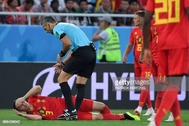 Slovenian referee Damir Skomina checks on Belgium's defender Thomas Vermaelen after resulting injured during the Russia 2018 World Cup Group G...