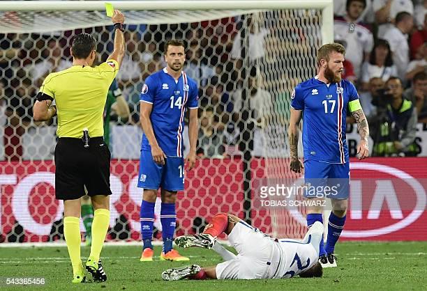 Slovenian referee Damir Skomina gives a yelow card against Iceland's midfielder Aron Gunnarsson as Iceland's defender Kari Arnason looks on during...
