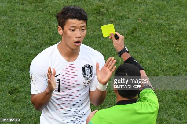 Slovenian referee Joel Aguilar presents South Korea's forward Hwang Heechan with a yellow card during the Russia 2018 World Cup Group F football...
