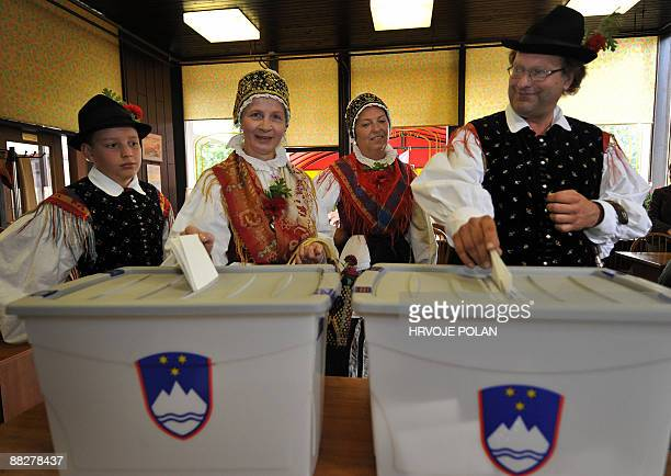 Slovenians in traditional dress vote during the elections for the European Parliament at the polling station in Radovljica some 50 kilometres north...