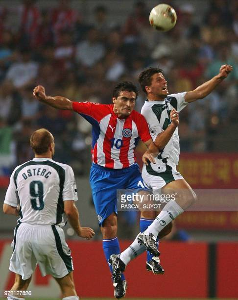 Slovenia's Amir Karic vies for the header with Paraguay's Roberto Acuna as Slovenia's Milan Osterc looks on 12 June 2002 at the Jeju World Cup...