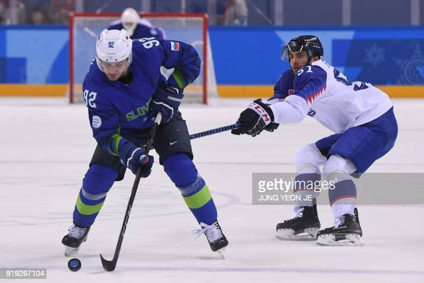 TOPSHOT Slovenia's Anze Kuralt and Slovakia's Dominik Granak fight for the puck in the men's preliminary round ice hockey match between Slovakia and...