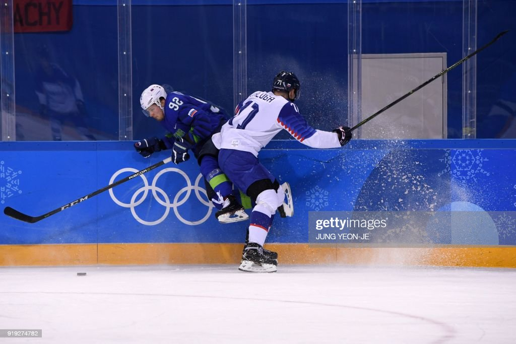 TOPSHOT - Slovenia's Anze Kuralt (L) and Slovakia's Marek Daloga fight for the puck in the men's preliminary round ice hockey match between Slovakia and Slovenia during the Pyeongchang 2018 Winter Olympic Games at the Kwandong Hockey Centre in Gangneung on February 17, 2018. / AFP PHOTO / JUNG Yeon-Je