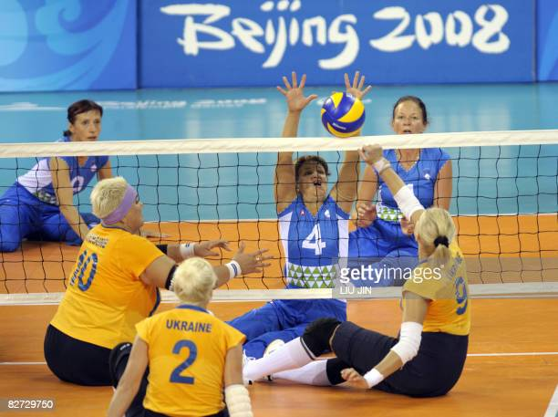 Slovenia's Bogomira Jakin defends against Ukraine players in their women's sitting volleyball preliminary match during the 2008 Beijing Paralympic...