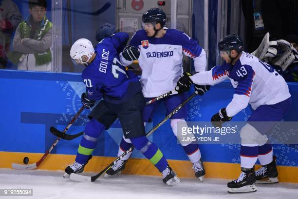 Slovenia's Bostjan Golicic and Slovakia's Peter Ceresnak fight for the puck, as Slovakia's Tomas Surovy watches, in the men's preliminary round ice...
