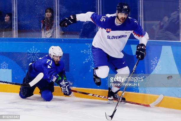 TOPSHOT Slovenia's Bostjan Golicic fights for the puck with Slovakia's Juraj Valach in the men's preliminary round ice hockey match between Slovakia...
