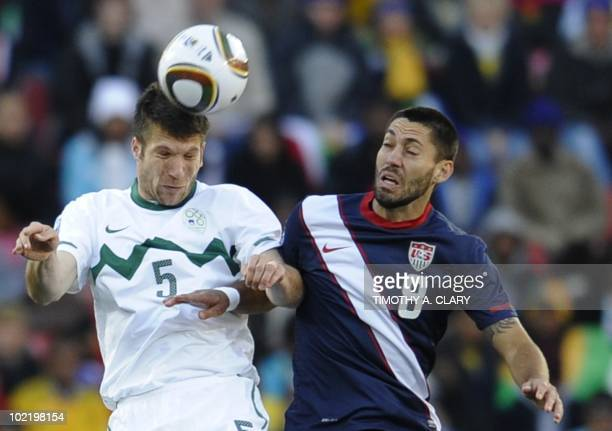 Slovenia's defender Bostjan Cesar heads the ball with US midfielder Clint Dempsey during their Group C first round 2010 World Cup football match on...