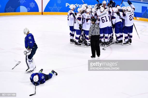 TOPSHOT Slovenia's Gasper Kroselj and Slovenia's Jan Urbas react as Team Norway celebrates their overtime win in the men's playoff qualifications ice...