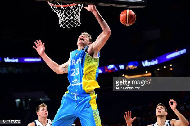 Slovenia's guard Luka Doncic and guard Aleksej Nikolic look on as Ukraine's center Artem Pustovyi jumps up to shoot the ball during the FIBA...