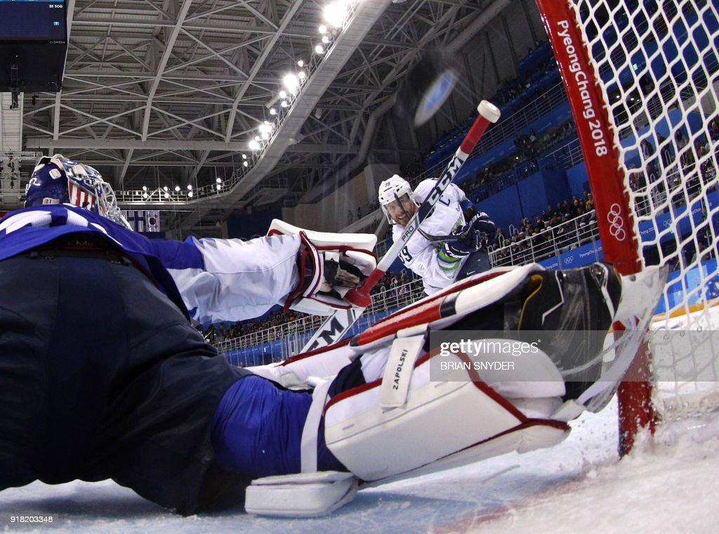 Slovenia's Jan Mursak (R) watches as the puck goes into the net to win in overtime in the men's preliminary round ice hockey match between Slovakia and Olympic Athletes from Russia during the Pyeongchang 2018 Winter Olympic Games at the Gangneung Hockey Centre in Gangneung on February 14, 2018. / AFP PHOTO / POOL / Brian SNYDER