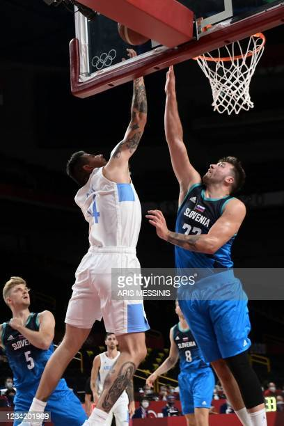 Slovenia's Luka Doncic and Argentina's Gabriel Deck jump for a rebound during the men's preliminary round group C basketball match between Argentina...