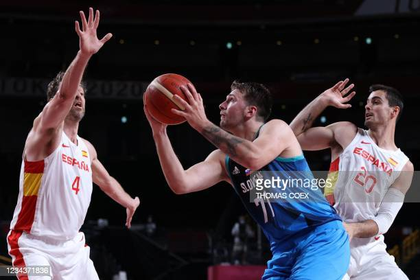 Slovenia's Luka Doncic shoots the ball past Spain's Pau Gasol Saez and Alberto Abalde in the men's preliminary round group C basketball match between...