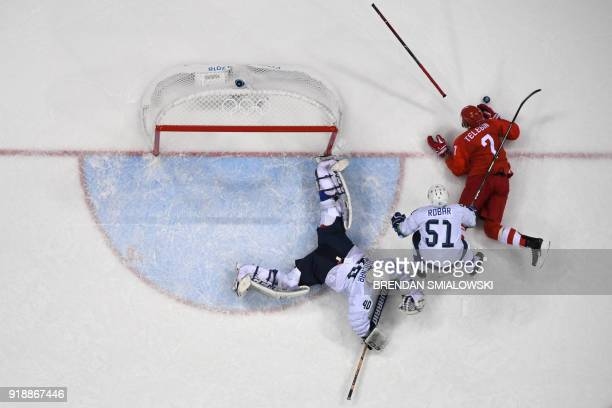 Slovenia's Luka Gracnar and Mitja Robar fight with Russia's Ivan Telegin for the puck in the men's preliminary round ice hockey match between the...