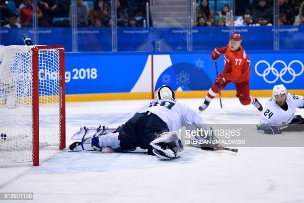 Slovenia's Luka Gracnar and Rok Ticar watch as Russia's Kirill Kaprizov scores in the men's preliminary round ice hockey match between the Olympic...