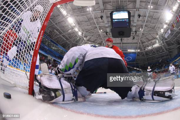 Slovenia's Luka Gracnar lets in a goal by Russia's Kirill Kaprizov in the men's preliminary round ice hockey match between the Olympic Athletes from...