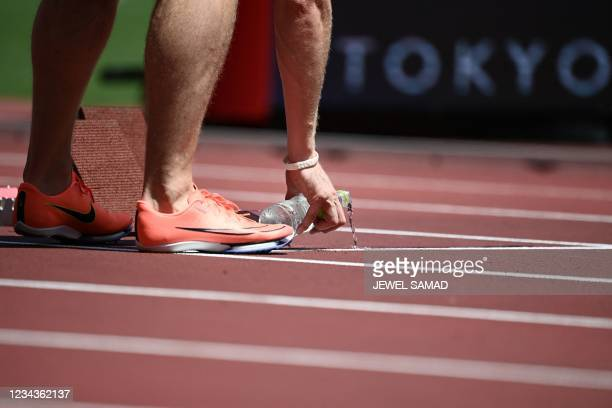 Slovenia's Luka Janezic pours water on the track before competing in the men's 400m heats during the Tokyo 2020 Olympic Games at the Olympic Stadium...