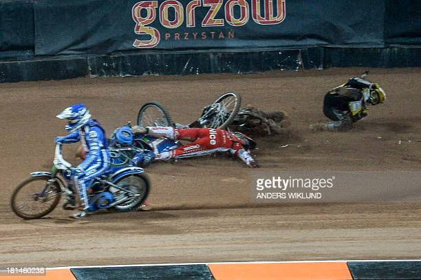 Slovenia's Matej Zagar passes by Poland's Tomasz Gollob who lies on the track while Great Britain's Tai Woffinden tries to get up after a collision...