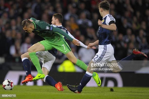 Slovenia's midfielder Josip Ilicic vies with Scotland's defender ANdrew Robertson and Scotland's defender Kieran Tierney during the World Cup 2018...