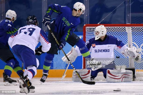 Slovenia's Miha Verlic watches as teammate Slovenia's Anze Kuralt scores in the men's preliminary round ice hockey match between Slovakia and...
