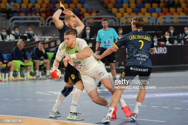 Slovenia's pivot Blaz Blagotinsek is challenged by Sweden's centre back Jim Gottfridsson and Sweden's left back Jonathan Carlsbogard during the 2021...
