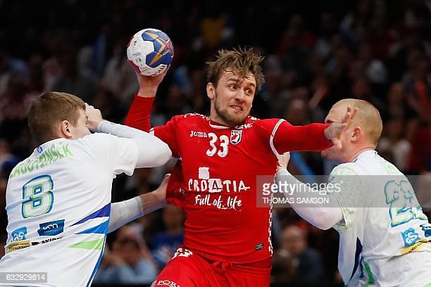 Slovenia's pivot Matej Gaber and Slovenia's wing Blaz Janc defend against Croatia's centre back Luka Cindric during the 25th IHF Men's World...