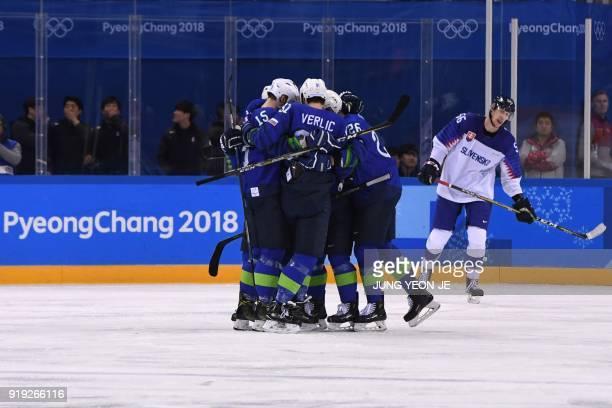 Slovenia's players celebrate teammate Anze Kuralt's goal as Slovakia's Michal Cajkovsky skates past in the men's preliminary round ice hockey match...