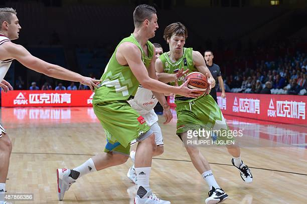Slovenia's point guard Jaka Klobucar passes the ball to Slovenia's center Alen Omic during the round of 16 basketball match between Latvia and...