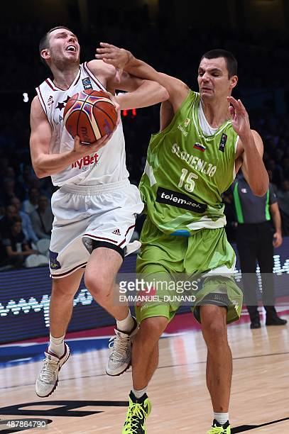 Slovenia's power forward Jure Balazic defends against Latvia's shooting guard Dairis Bertans during the round of 16 basketball match between Latvia...