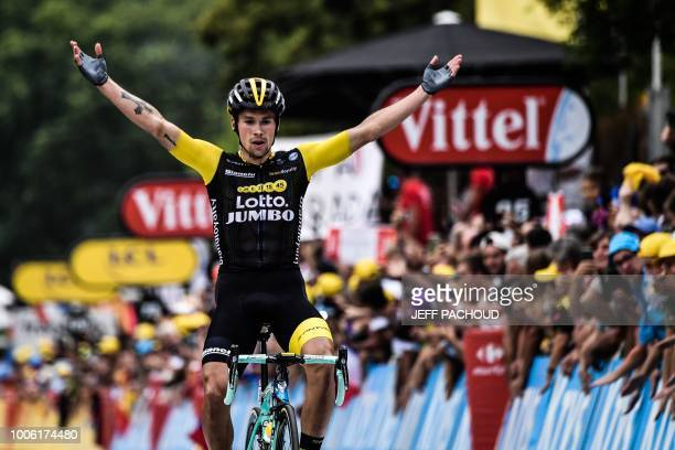 TOPSHOT Slovenia's Primoz Roglic celebrates as he crosses the finish line to win the 19th stage of the 105th edition of the Tour de France cycling...