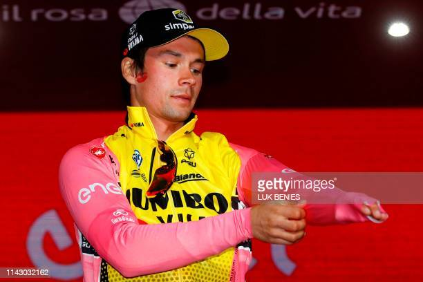 Slovenia's Primoz Roglic puts on the overall leader's pink jersey on the podium after winning the first stage of the 2019 Giro d'Italia the cycling...