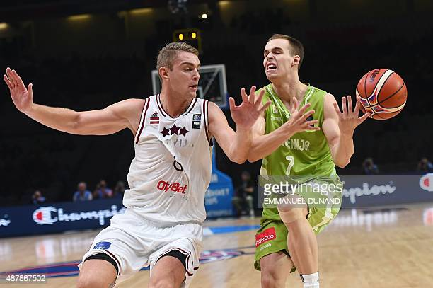 Slovenia's shooting guard Klemen Prepelic misses the ball next to Latvia's power forward Rolands Freimanis during the round of 16 basketball match...