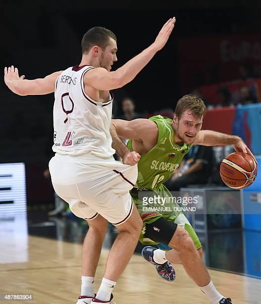 Slovenia's small forward Zoran Dragic works around Latvia's shooting guard Dairis Bertans during the round of 16 basketball match between Latvia and...