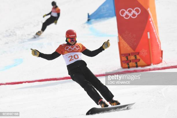Slovenia's Zan Kosir finishes ahead of Germany's Stefan Baumeister in a quarterfinal heat of the men's snowboard parallel giant slalom event at the...