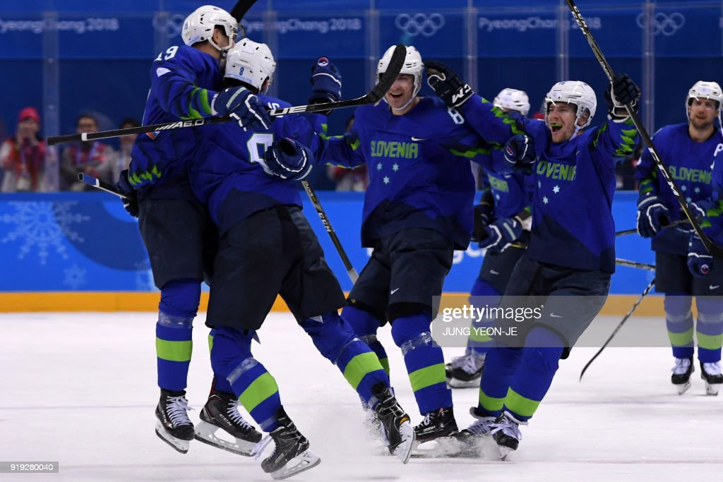 Slovenia's Ziga Jeglic (2nd L) is congratulated by teammates after scoring the game winning goal in a penalty-shot shootout in the men's preliminary round ice hockey match between Slovakia and Slovenia during the Pyeongchang 2018 Winter Olympic Games at the Kwandong Hockey Centre in Gangneung on February 17, 2018. / AFP PHOTO / JUNG Yeon-Je