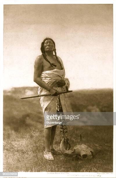 Slow Bull, full-length portrait, facing front, holding pipe, buffalo skull at his feet.
