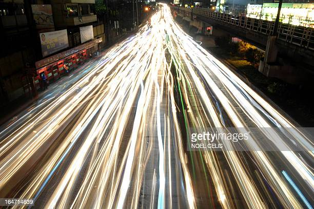A slow shutter effect shows lights from private and passenger vehicles in traffic on EDSA highway in Manila on March 27 2013 Many Filipinos spend the...