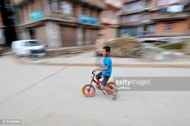 A slow shutter in a panning technique of a kid playing in a cycle around the premises of chyasal Patan Nepal on Saturday September 24 2016