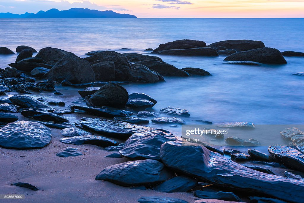 Slow shutter speed capture of the surf pounding on rocks : Stock Photo