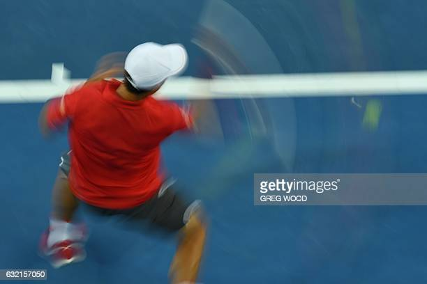 A slow shutter speed exposure shows Japan's Kei Nishikori hitting a return against Slovakia's Lukas Lacko during their men's singles third round...