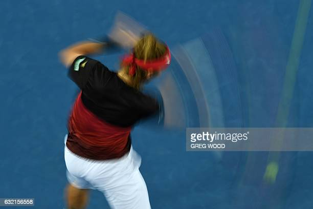 A slow shutter speed exposure shows Slovakia's Lukas Lacko hitting a return against Japan's Kei Nishikori during their men's singles third round...