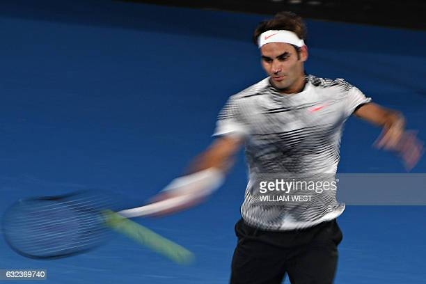 A slow shutter speed exposure shows Switzerland's Roger Federer hitting a return against Japan's Kei Nishikori during their men's singles fourth...