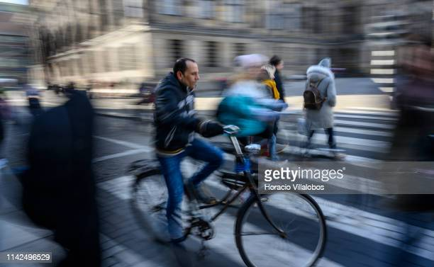 Slow shutter speed photo of cyclists riding near the Royal Palace on April 13, 2019 in Amsterdam, The Netherlands. The number of visitors, some ten...