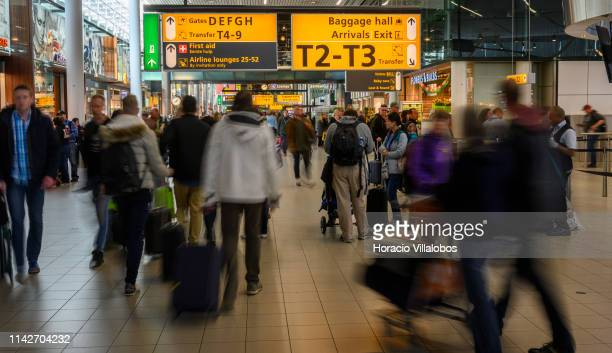 Slow shutter speed photo of travelers walking under Information signs in Lounge 1 of Schiphol International Airport on April 14 2019 in Amsterdam The...