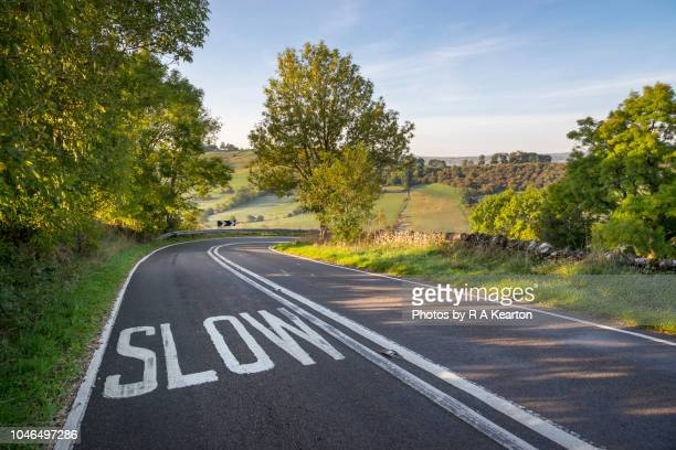 slow sign on sharp bend of a country road - 遅い ストックフォトと画像