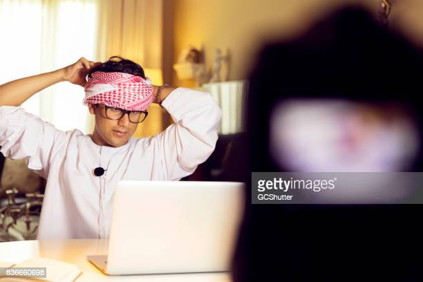 Slowly wearing an Arab headscarf on camera to show the viewers of his vlog how to wear one properly