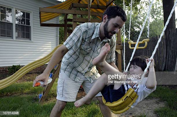 Manny Date 7202006 Kevin Clark/The Washington Post Neg # 182340 Alexandria VA Adam Good tries to spray insect repellent on Jacob Solomon at their...